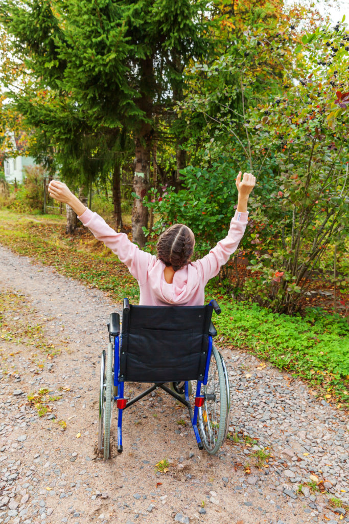 Photo of a young woman using a wheelchair. She is wearing pink and has her arms up in the air.
